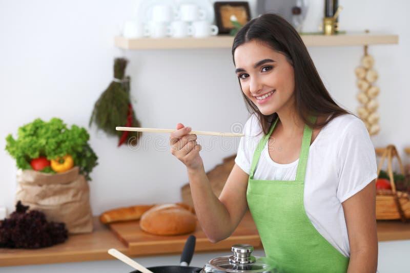 La mujer hispánica joven está cocinando en la cocina imagen de archivo