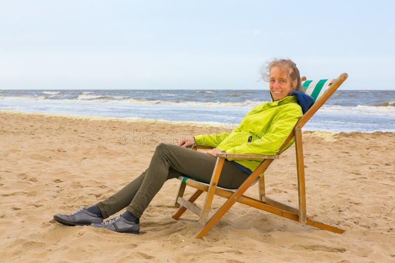 La mujer holandesa se sienta en silla de playa por el mar fotografía de archivo libre de regalías