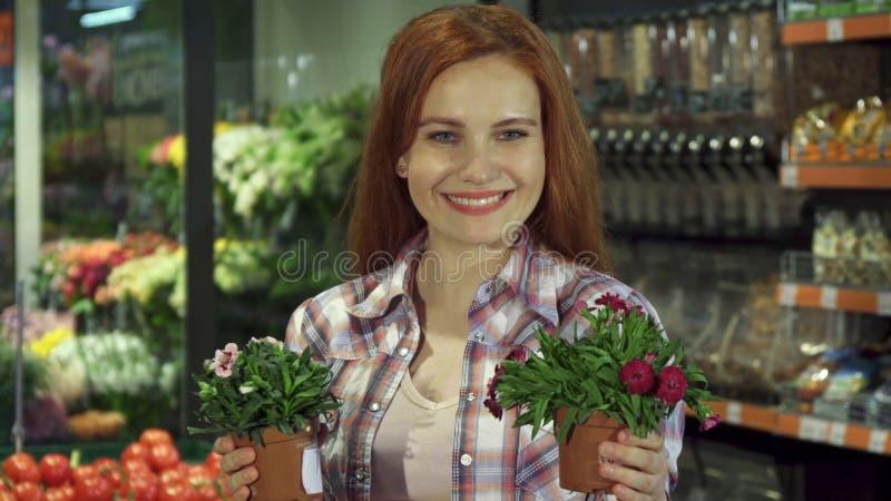La mujer huele diversas plantas de la casa en el supermercado imagen de archivo