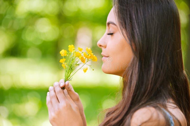 La mujer huele los floretes amarillos fotos de archivo libres de regalías