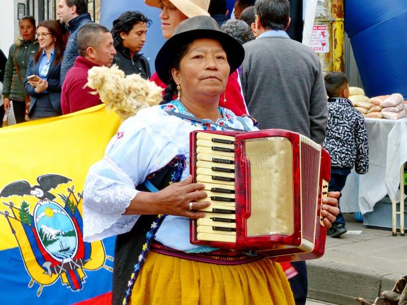 La mujer indígena juega en el acordeón, Ecuador foto de archivo