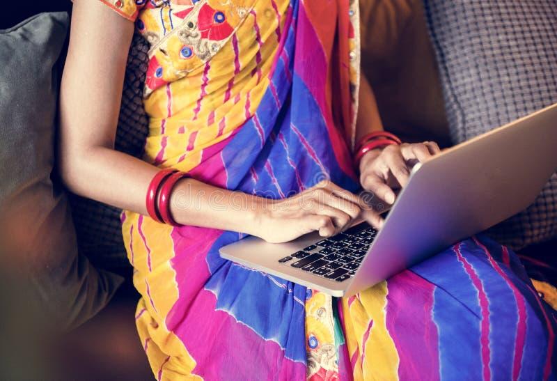 La mujer india está utilizando el ordenador portátil del ordenador foto de archivo libre de regalías