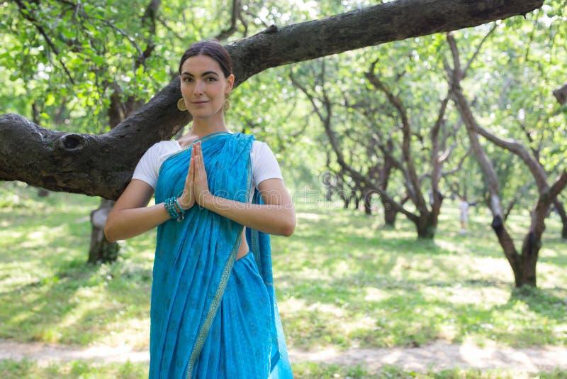 La mujer india joven hermosa se vistió en la rogación y el medit de una sari fotografía de archivo
