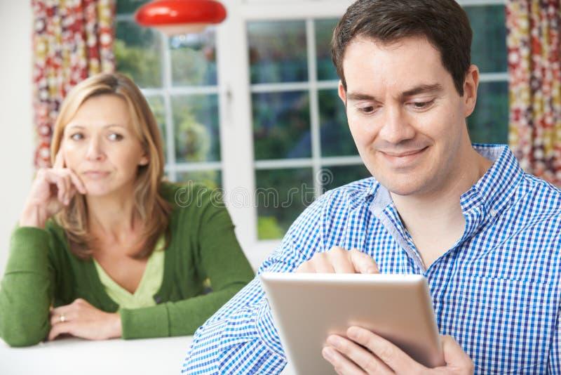 La mujer infeliz que se sienta en la tabla como socio utiliza la tableta de Digitaces foto de archivo libre de regalías
