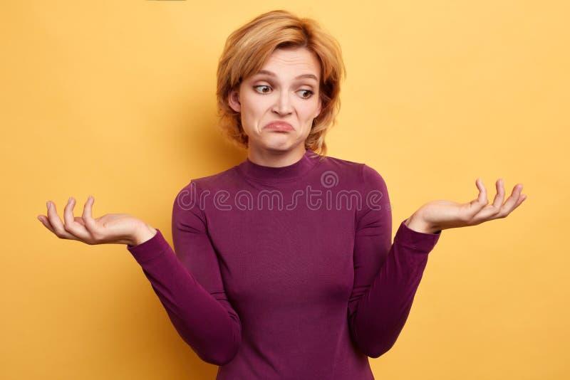 La mujer infeliz triste con las manos aumentadas no puede encontrar la solución del problema imagen de archivo libre de regalías