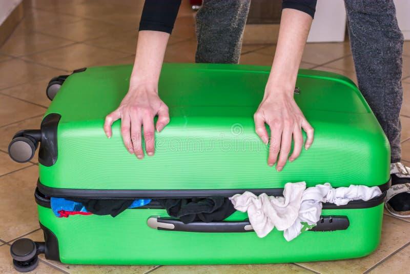 La mujer intenta cerrar la maleta sobrellenada imagen de archivo