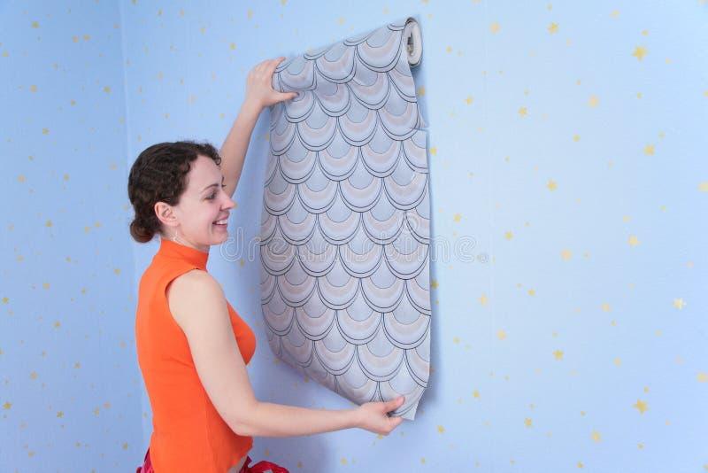La mujer intenta encendido los papeles pintados para emparedar imágenes de archivo libres de regalías