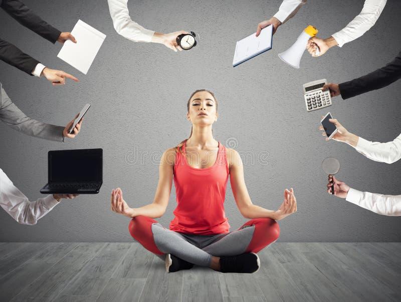 La mujer intenta mantener calma con yoga debida subrayar y trabajar demasiado en el wok foto de archivo