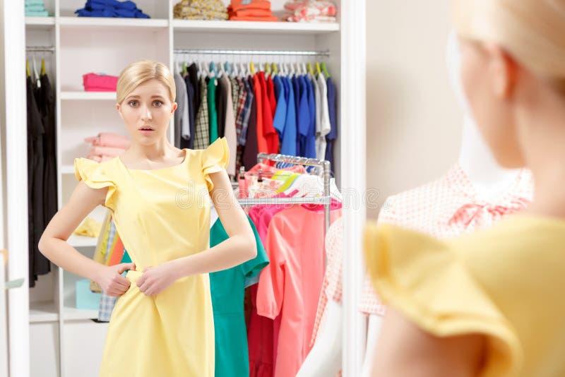 La mujer intenta un nuevo vestido en tienda imagenes de archivo