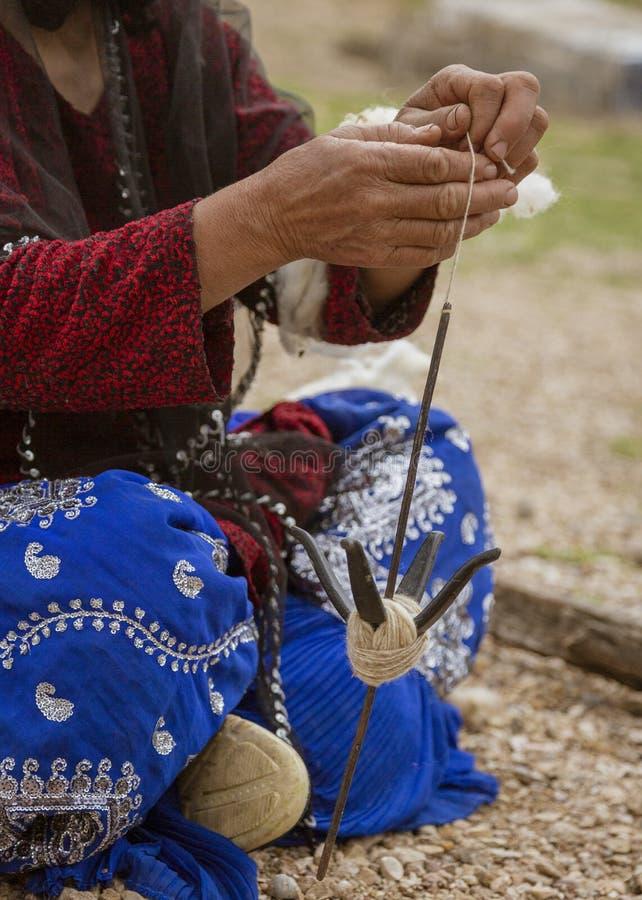 La mujer iraní de la tribu de la colina hace girar las lanas de la cabra - primer imagen de archivo