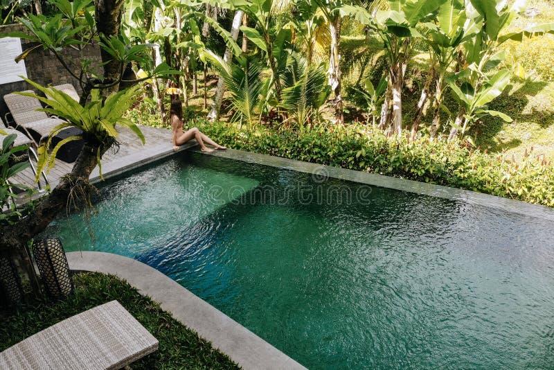 La mujer irreconocible en el bikini que se sienta al borde de piscina en Bali admira una hermosa vista de las palmeras lujo imagenes de archivo
