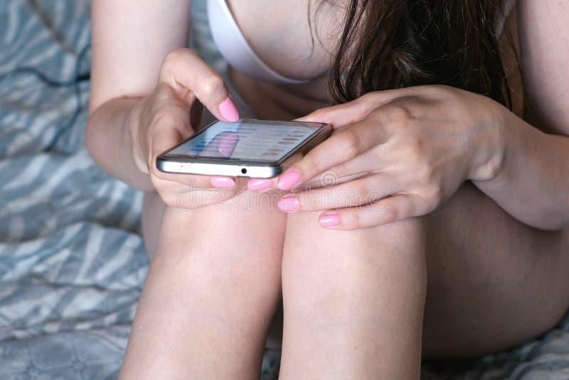 La mujer irreconocible en ropa interior mecanografía un mensaje en un teléfono móvil imagenes de archivo