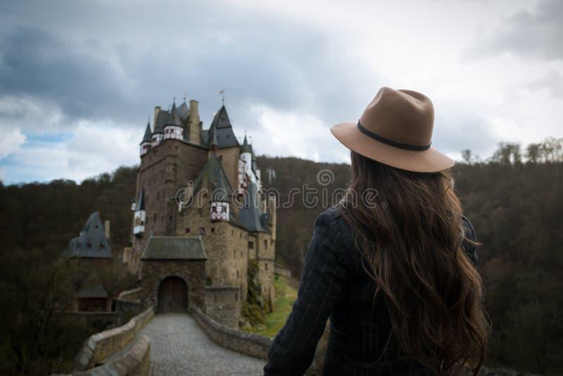 La mujer irreconocible joven camina a lo largo del camino que lleva a un castillo increíble foto de archivo