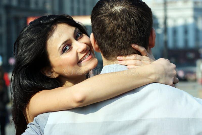 La mujer joven abraza al individuo imagen de archivo
