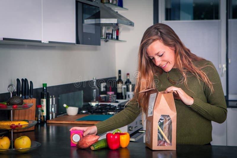 La mujer joven abre un paquete de ingredientes frescos para hacer una cena sana fotos de archivo libres de regalías