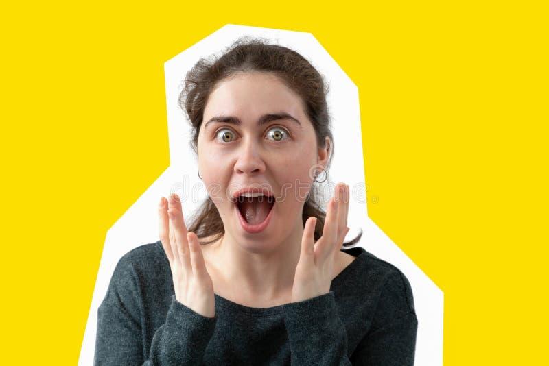 La mujer joven abrió su boca en sorpresa Fondo amarillo El concepto de publicidad Copie el espacio foto de archivo
