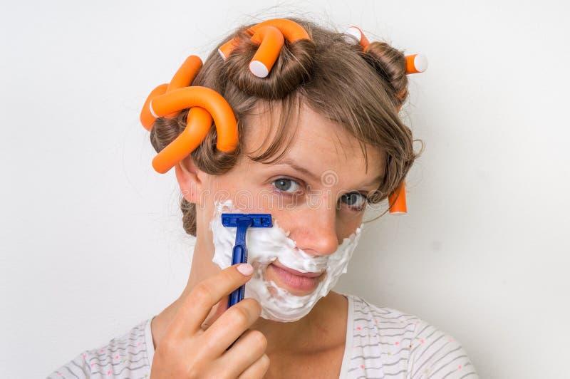 La mujer joven afeita su cara con espuma y la maquinilla de afeitar fotografía de archivo libre de regalías