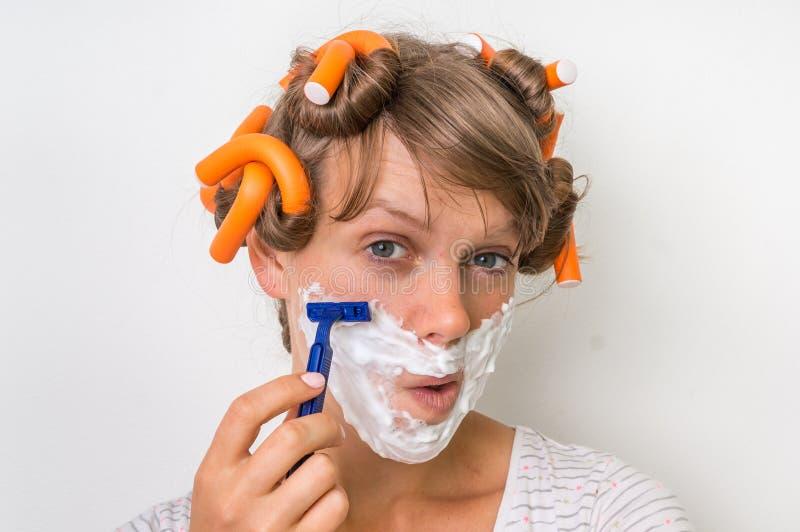 La mujer joven afeita su cara con espuma y la maquinilla de afeitar imágenes de archivo libres de regalías