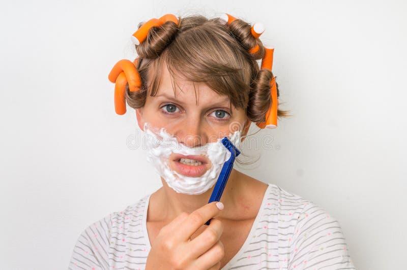 La mujer joven afeita su cara con espuma y la maquinilla de afeitar foto de archivo libre de regalías