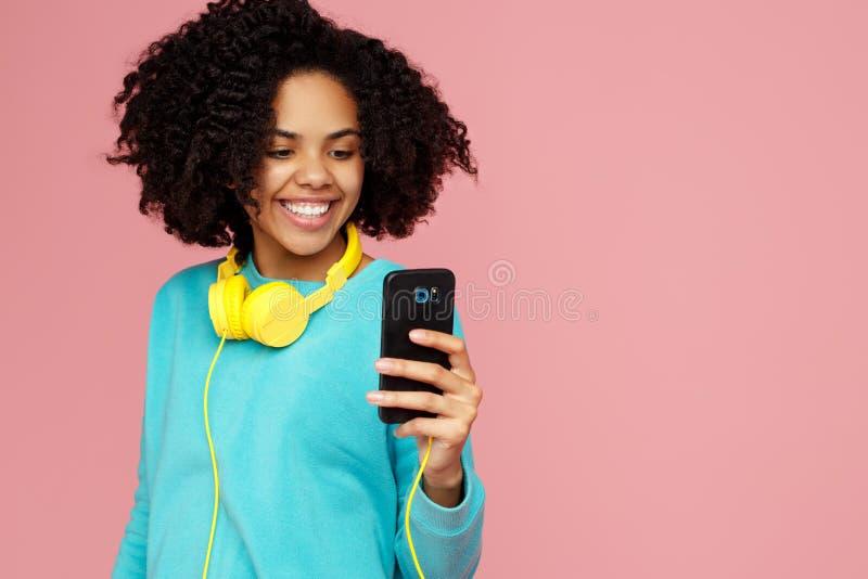 La mujer joven afroamericana atractiva con sonrisa brillante vestida en ropa casual toma la imagen con smartphone encima foto de archivo