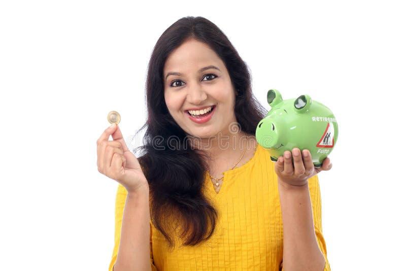 La mujer joven ahorra el dinero en la hucha fotografía de archivo libre de regalías