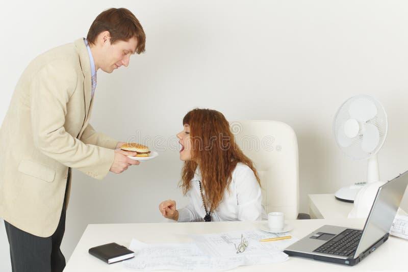 La mujer joven alcanza cómicamente para la comida durante imagenes de archivo