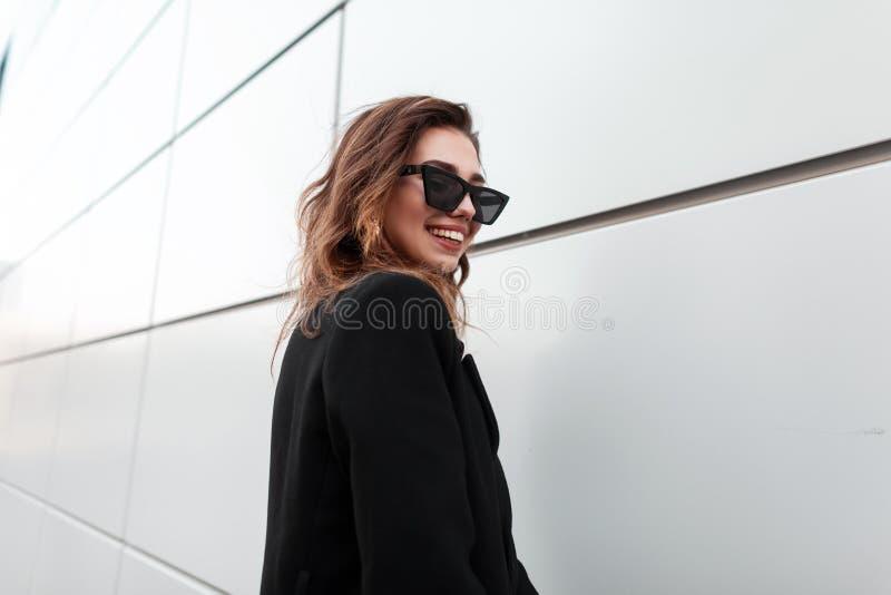 La mujer joven alegre bonita del inconformista en gafas de sol oscuras con una sonrisa hermosa en una capa elegante negra se está imagen de archivo libre de regalías