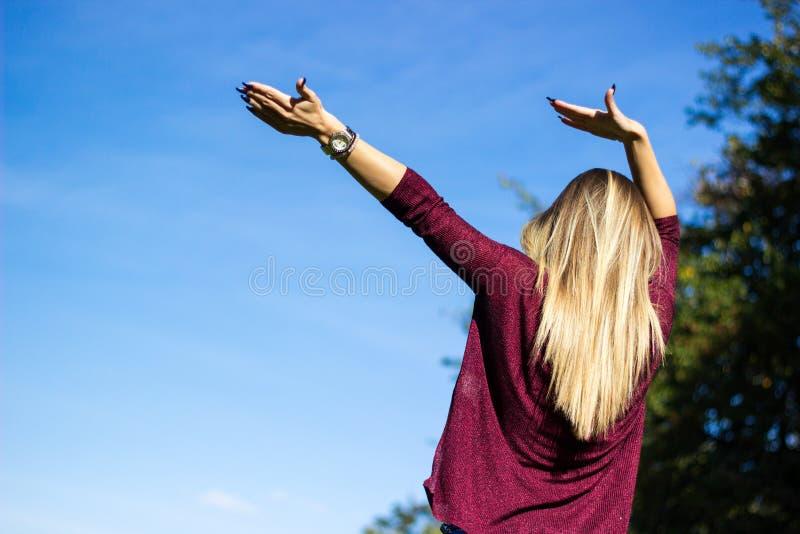 La mujer joven alegre con las manos aumentó hacia el cielo imagen de archivo libre de regalías