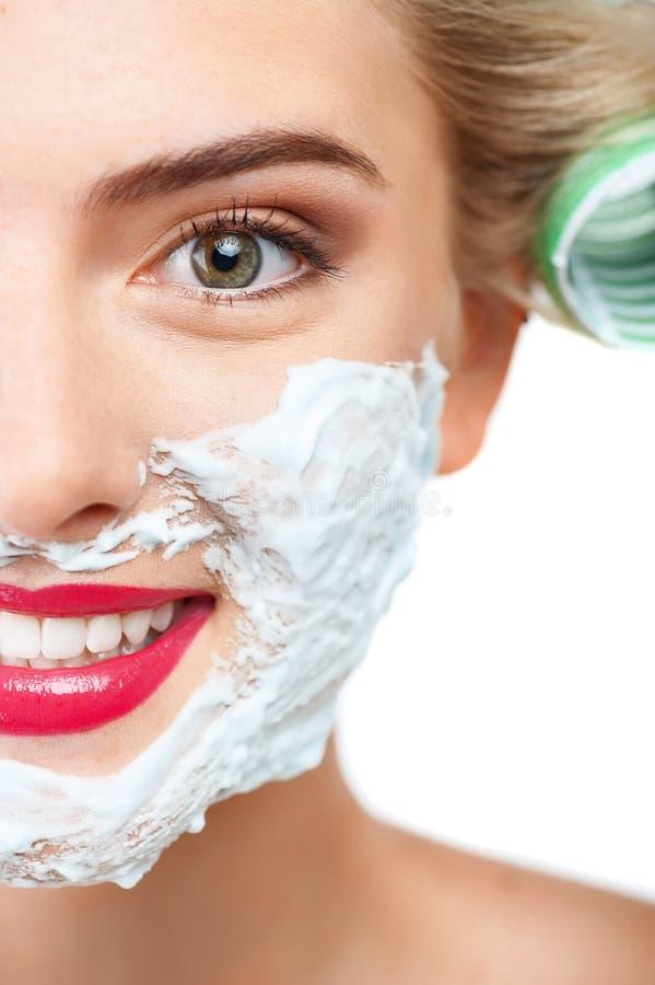 La mujer joven alegre con sonrisa bonita está afeitando foto de archivo