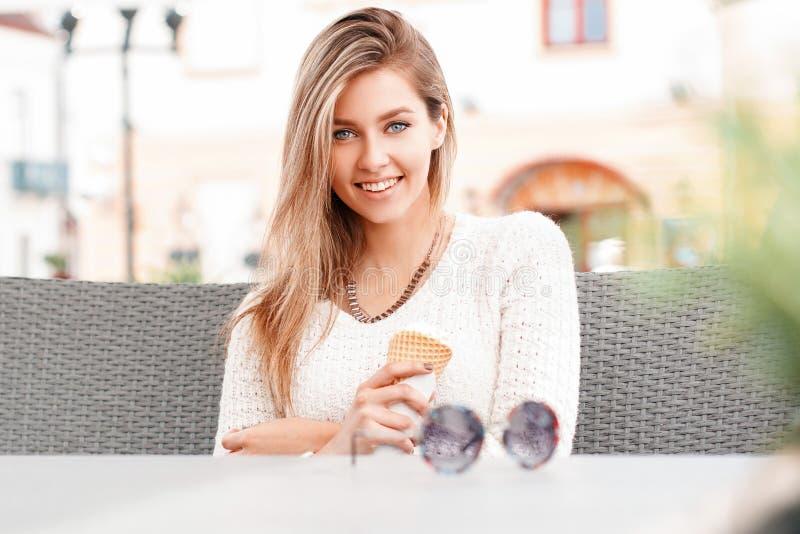 La mujer joven alegre feliz linda en sonrisa hermosa con los ojos azules con el pelo rubio en un suéter hecho punto se sienta y s foto de archivo