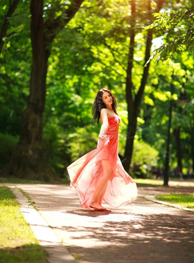 La mujer joven alegre goza el bailar en parque verde de la ciudad en la naturaleza entre los árboles, el concepto de libertad y e fotografía de archivo