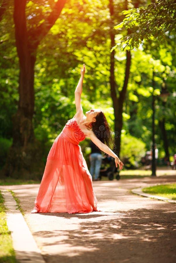 La mujer joven alegre goza el bailar en parque verde de la ciudad en la naturaleza entre los árboles, el concepto de libertad y e fotos de archivo