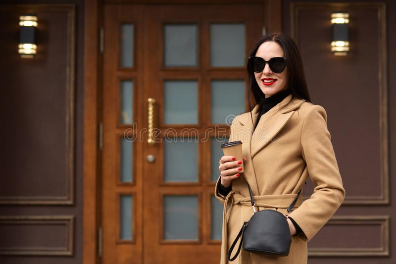 La mujer joven alegre que lleva la capa beige, suéter negro, tiene bolso y las gafas de sol, bebiendo el café para llevar en taza fotos de archivo