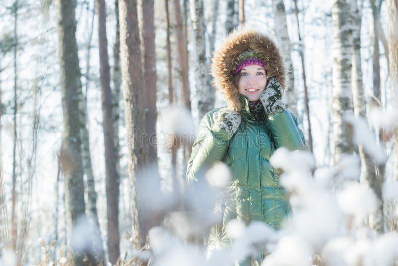 La mujer joven alegre que sostiene las manoplas lanosas acerca a su cabeza en bosque del invierno al aire libre foto de archivo