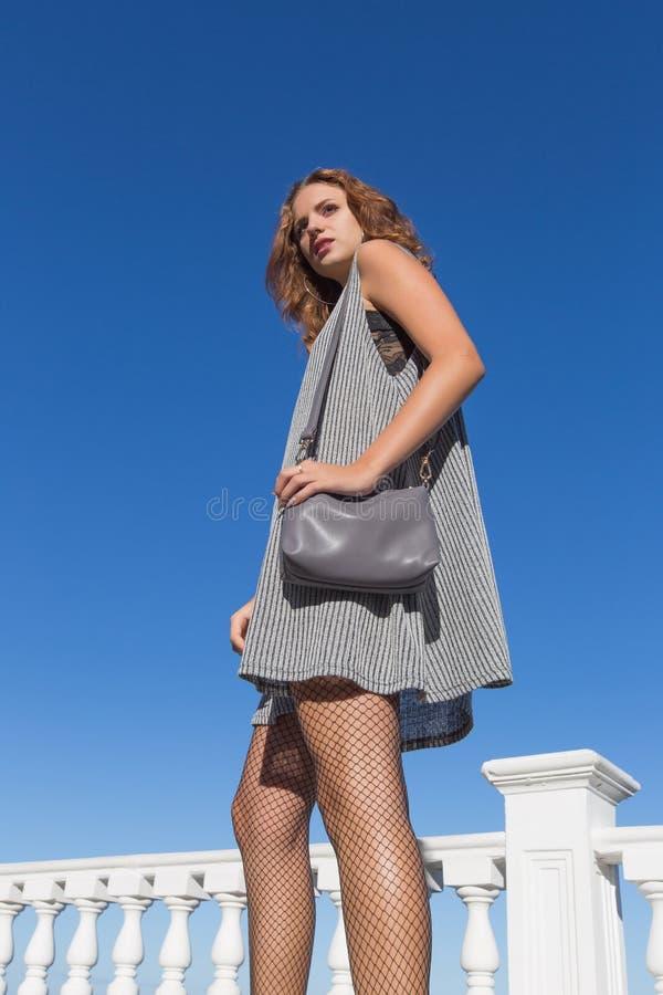 La mujer joven alta camina contra el cielo fotografía de archivo