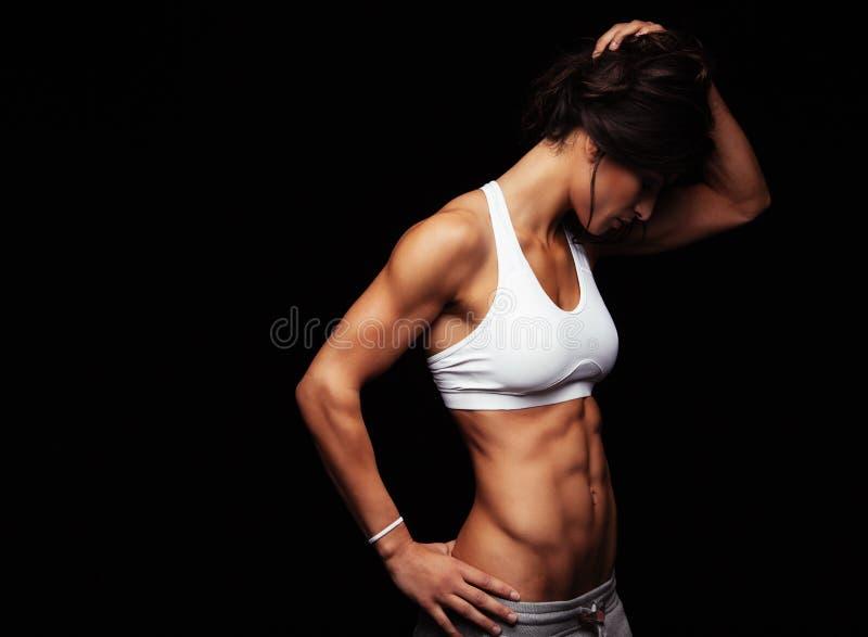 La mujer joven apta en deportes lleva la mirada abajo foto de archivo libre de regalías