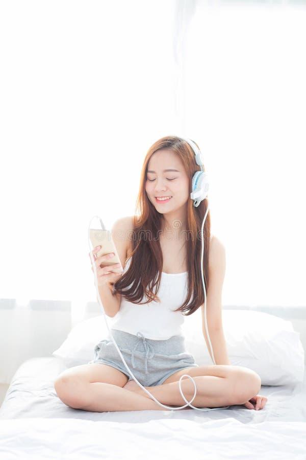 La mujer joven asiática hermosa goza escucha música con el auricular y sostener el teléfono móvil elegante mientras que se sienta fotografía de archivo libre de regalías