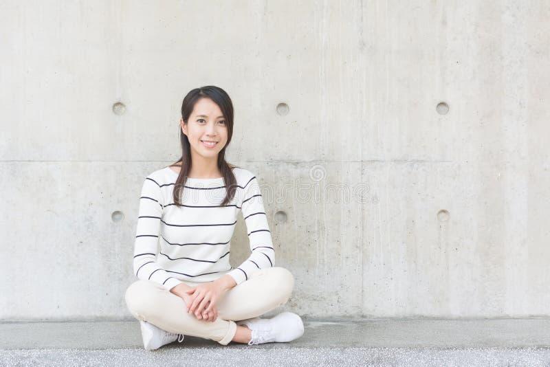 La mujer joven asiática se sienta foto de archivo libre de regalías