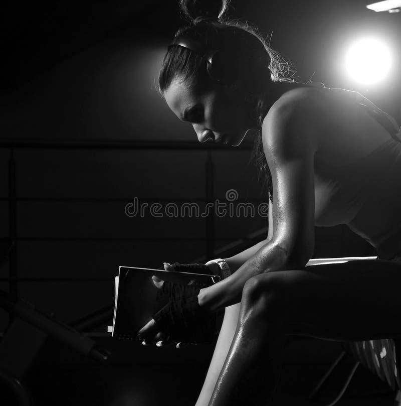 La mujer joven atlética que se sienta con el libro del calendario de la aptitud hace notas Gimnasio sano del entrenamiento de la  imagenes de archivo
