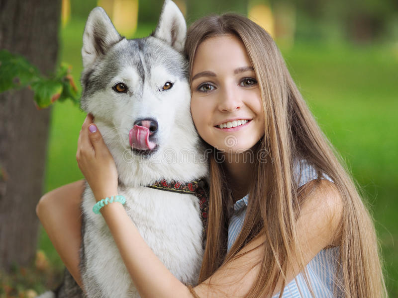 La mujer joven atractiva abraza el perro divertido del husky siberiano con los ojos marrones imagen de archivo libre de regalías