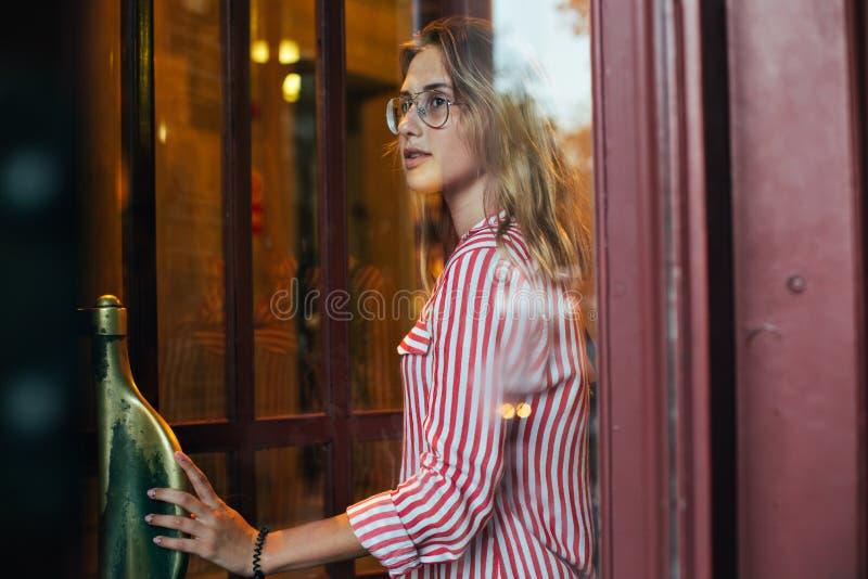 La mujer joven atractiva camina a través de puertas giratorias foto de archivo