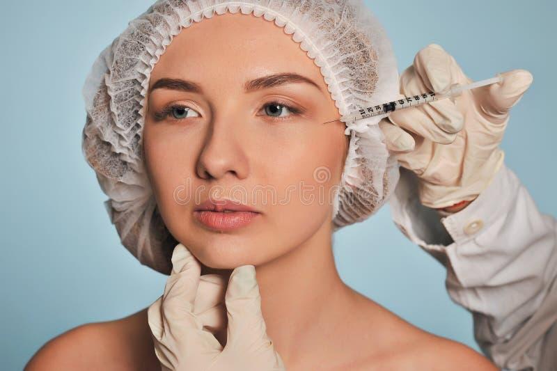 La mujer joven atractiva consigue la inyección cosmética imagen de archivo
