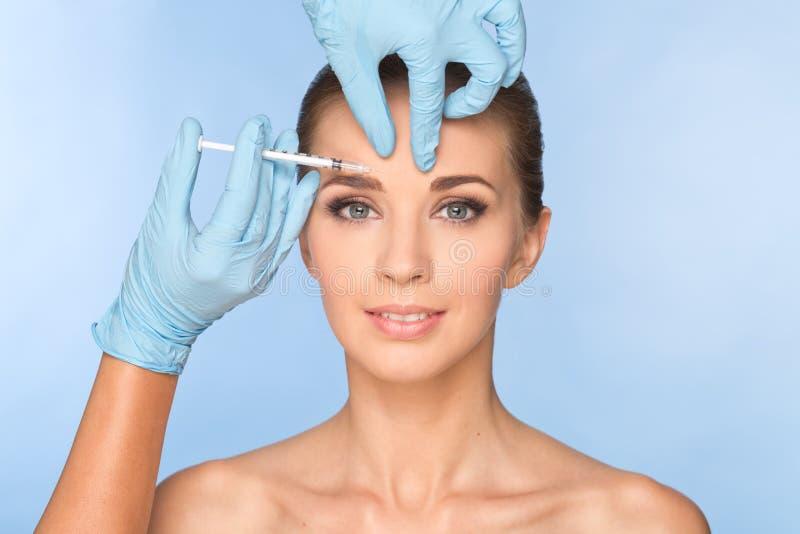 La mujer joven atractiva consigue la inyección cosmética del botox foto de archivo libre de regalías