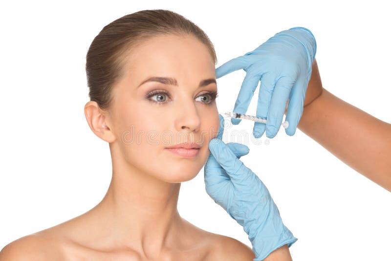 La mujer joven atractiva consigue la inyección cosmética del botox imagen de archivo