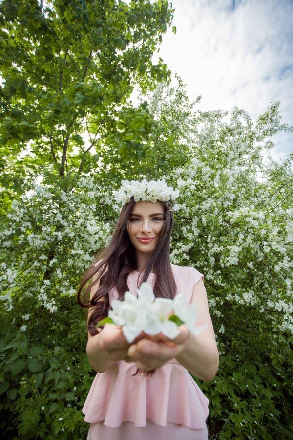 La mujer joven atractiva en flores enrruella en jardín del flor de la primavera al aire libre Retrato al aire libre de la muchach imagenes de archivo