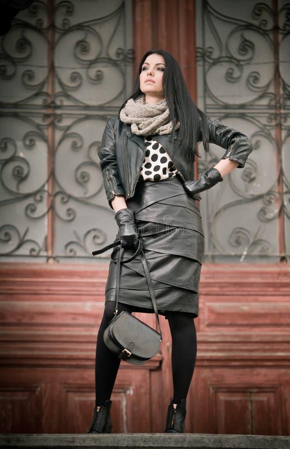 La mujer joven atractiva en tiro de la moda del invierno con hierro labrado adornó puertas en fondo. Hembra de moda hermosa imágenes de archivo libres de regalías