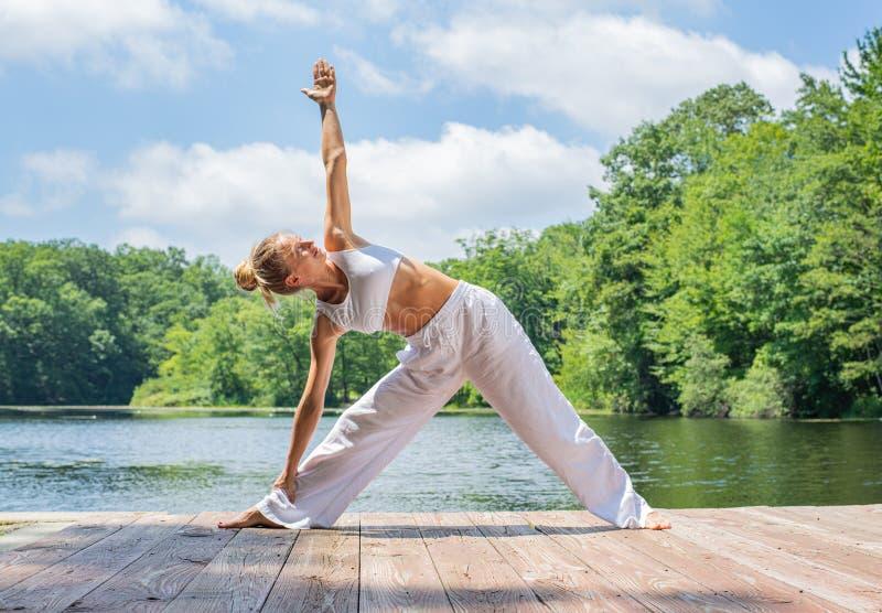 La mujer joven atractiva está practicando la yoga, haciendo la actitud de Utthita Trikonasana cerca del lago imagen de archivo