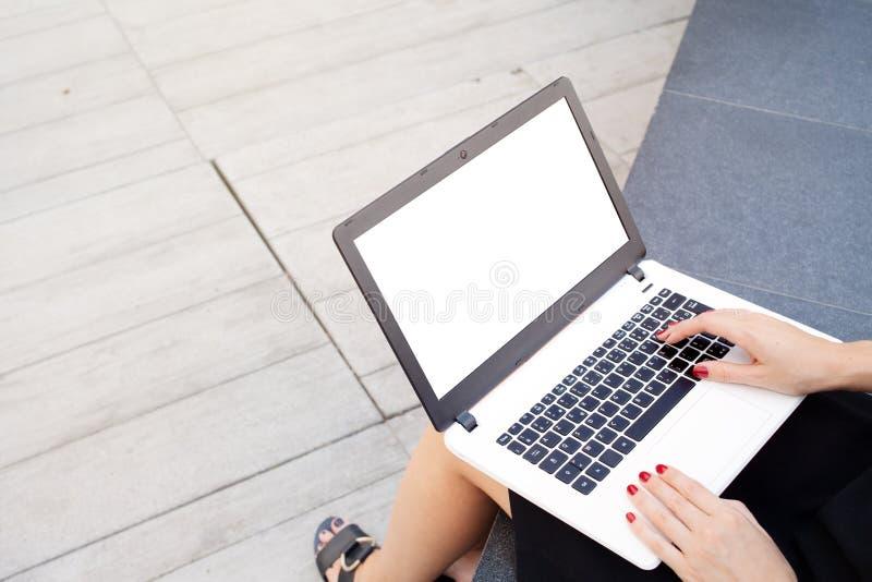 La mujer joven atractiva está trabajando en el ordenador portátil imagen de archivo