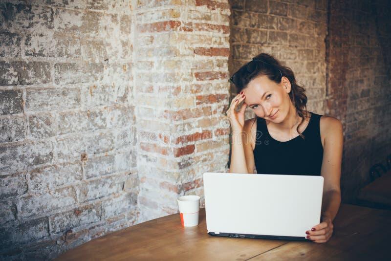 La mujer joven atractiva está trabajando en el ordenador portátil mientras que se sienta en un café del desván La pared de ladril foto de archivo libre de regalías
