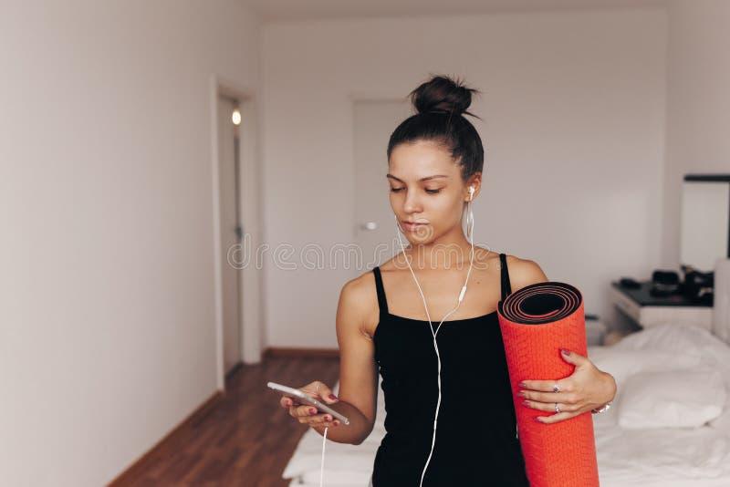 La mujer joven atractiva feliz se sostiene en estera roja de la yoga o de la aptitud de las manos después de resolver en casa en  fotos de archivo libres de regalías